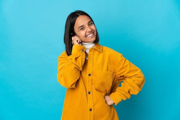 笑って青い背景で隔離の若いラテン女性