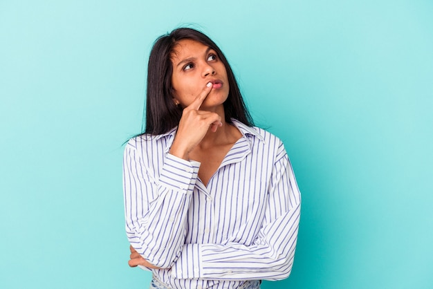 疑わしいと懐疑的な表情で横向きに青い背景で隔離の若いラテン女性。