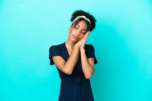 愛らしい表情で睡眠ジェスチャーを作る青い背景に分離された若いラテン女性