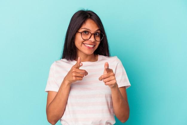 指で正面を指している青い背景に分離された若いラテン女性。