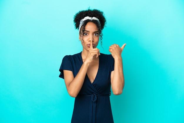 Молодая латинская женщина изолирована на синем фоне, указывая в сторону и делает жест молчания