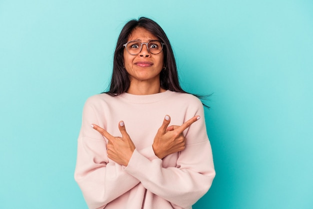Молодая латинская женщина, изолированная на синем фоне, указывает боком, пытается выбрать один из двух вариантов.