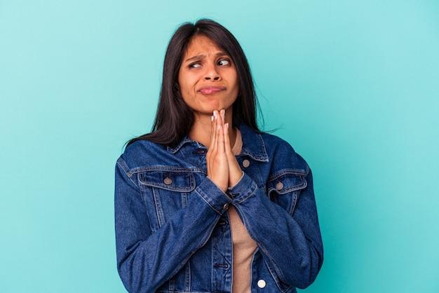 祈り、献身を示し、神のインスピレーションを探している宗教的な人を祈って青い背景で孤立した若いラテン女性。
