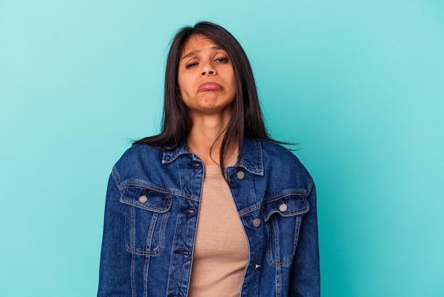 青の背景に孤立した若いラテン女性悲しい、深刻な顔、悲惨で不快な感じ。
