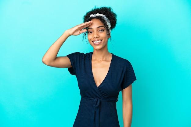 幸せな表情で手で敬礼青い背景で隔離の若いラテン女性