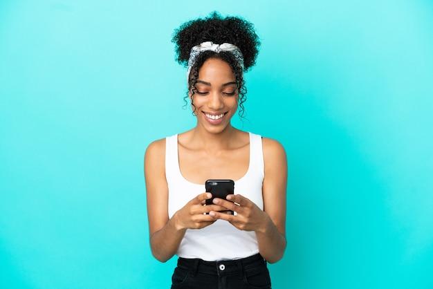 Молодая латинская женщина изолирована на синем фоне, отправляя сообщение с мобильного телефона