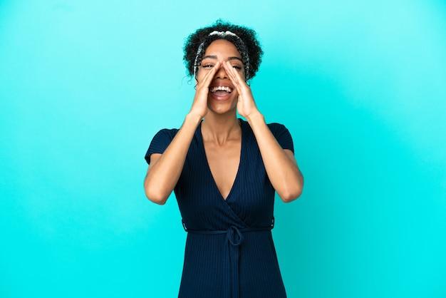 Молодая латинская женщина, изолированная на синем фоне, кричит и что-то объявляет