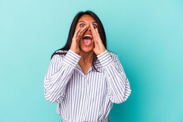 Молодая латинская женщина, изолированных на синем фоне крича, возбуждена к фронту.