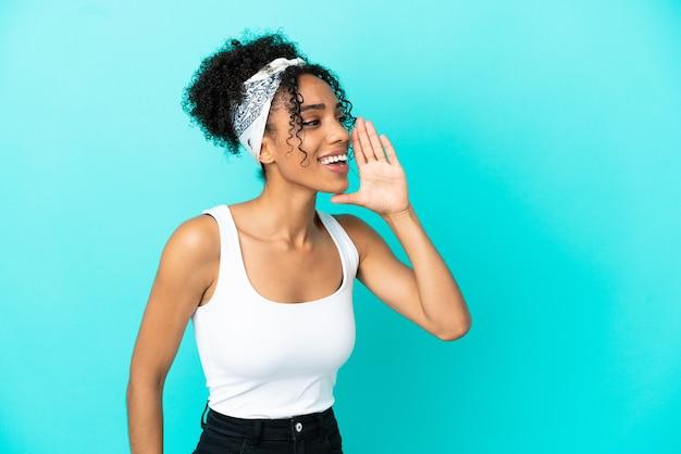 Молодая латинская женщина, изолированная на синем фоне, кричит с широко открытым ртом в сторону