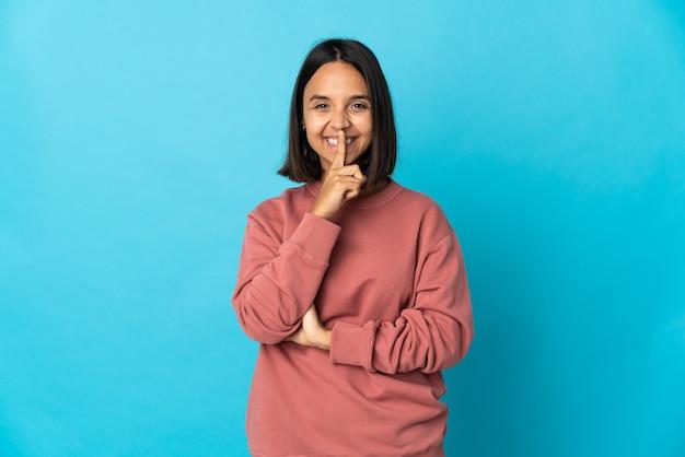 口に指を置く沈黙ジェスチャーの兆候を示す青い背景で隔離の若いラテン女性