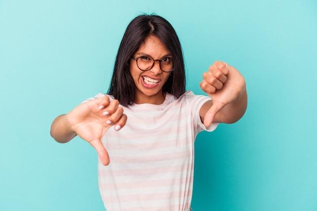 親指を下に表示し、嫌悪感を表現する青い背景で隔離の若いラテン女性。