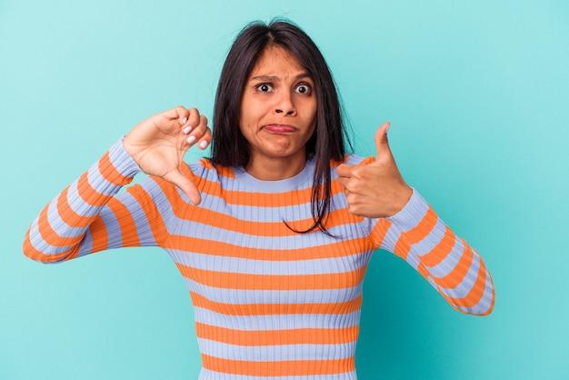 親指を上と親指を下に示す青い背景で隔離の若いラテン女性、難しい選択の概念