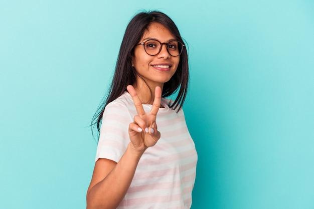 勝利の兆候を示し、広く笑顔で青い背景に分離された若いラテン女性。