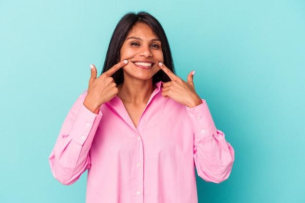 파란색 배경 미소에 고립 된 젊은 라틴 여자 입에 손가락을 가리키는.