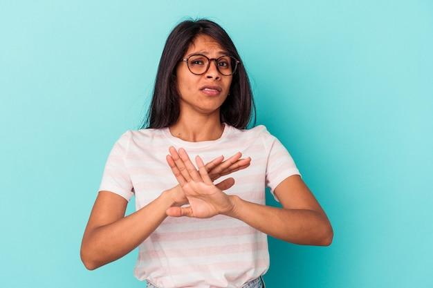 Молодая латинская женщина, изолированные на синем фоне, стоя с протянутой рукой, показывая знак остановки, предотвращая вас.