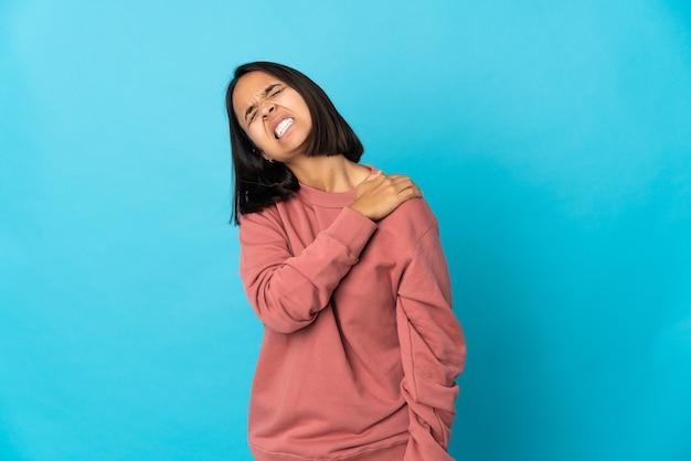 Молодая латинская женщина, изолированная на синем фоне, страдает от боли в плече из-за того, что приложила усилие