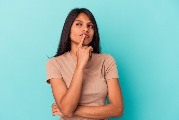 皮肉な表情でカメラを見て不幸な青い背景で隔離の若いラテン女性。