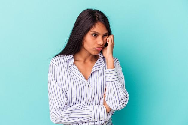 コピースペースを見て、悲しくて物思いにふける青い背景に孤立した若いラテン女性。