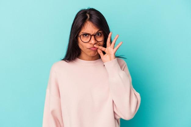 Молодая латинская женщина изолирована на синем фоне с пальцами на губах, сохраняя в секрете.