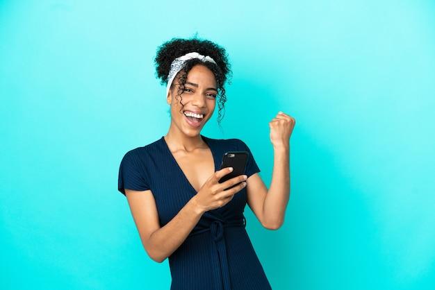 Молодая латинская женщина изолирована на синем фоне с телефоном в победной позиции