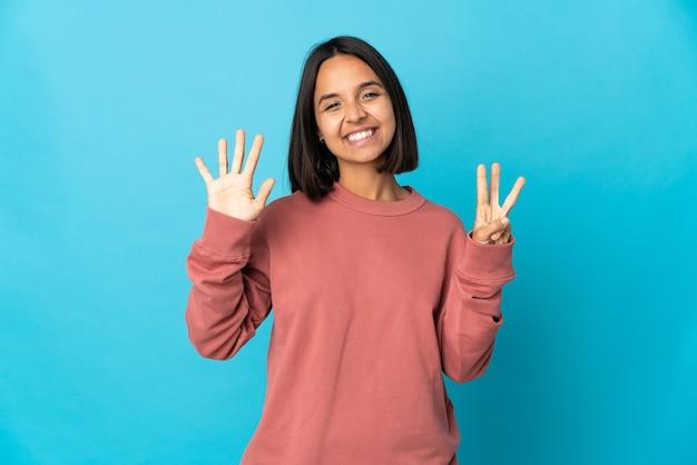 손가락으로 8 세 파란색 벽에 고립 된 젊은 라틴 여자