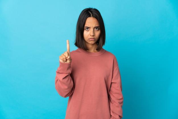 深刻な表情で1つを数える青い壁に分離された若いラテン女性