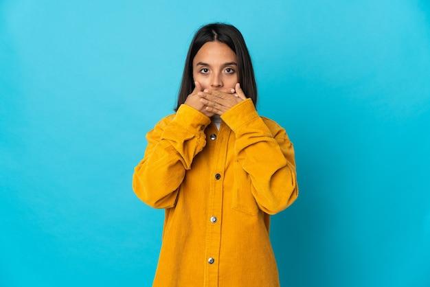 手で口を覆う青い壁に分離された若いラテン女性