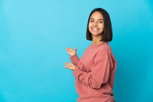 青い壁に孤立した若いラテン女性