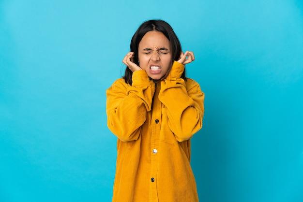 欲求不満と耳を覆っている青い壁に孤立した若いラテン女性