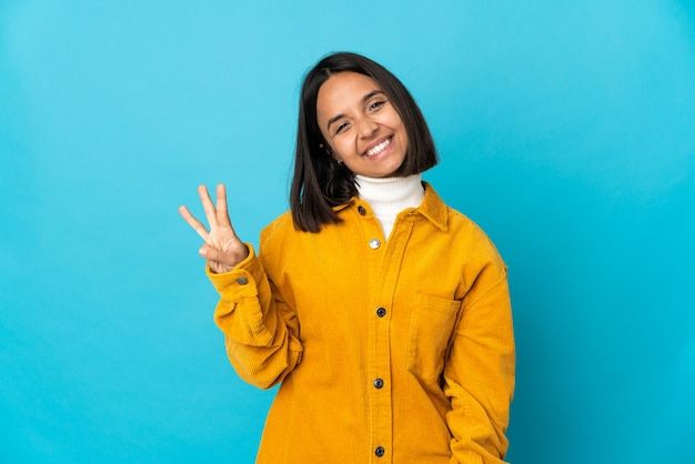 파란색 벽에 고립 된 젊은 라틴 여자 행복 하 고 손가락으로 세 세