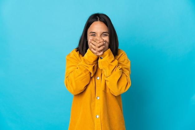 若いラテン女性は手で口を覆う幸せと笑顔の青い壁に分離