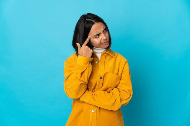 Молодая латинская женщина изолирована на синей стене, делая жест безумия, положив палец на голову