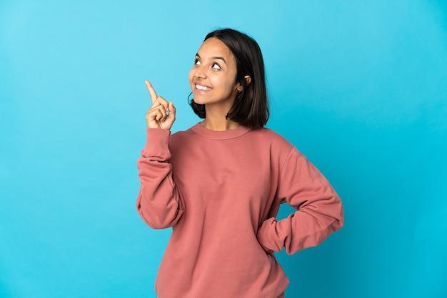 素晴らしいアイデアを指している青い壁に分離された若いラテン女性