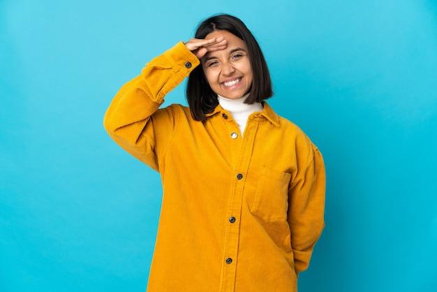 幸せな表情で手で敬礼青い壁に分離された若いラテン女性