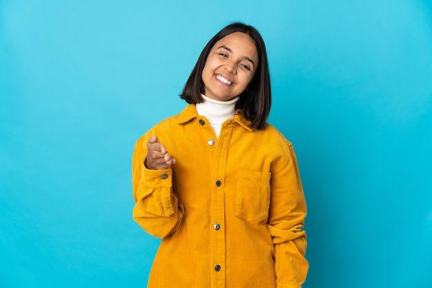 Молодая латинская женщина изолирована на синей стене, пожимая руку для заключения хорошей сделки