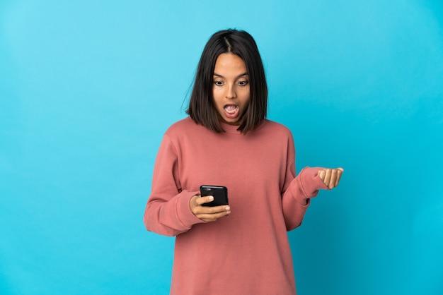 青い壁に孤立した若いラテン女性は驚いてメッセージを送信します