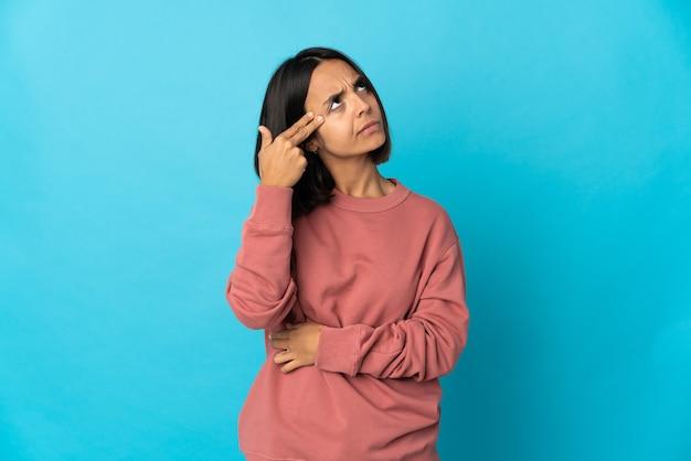 自殺ジェスチャーをする問題で青い壁に孤立した若いラテン女性