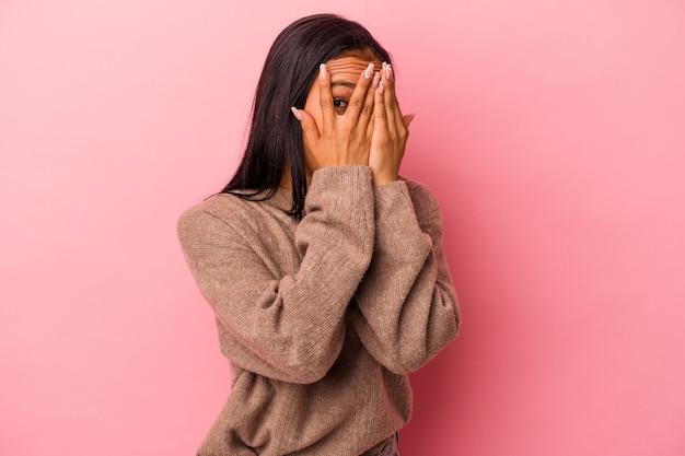 ピンクの背景に分離された若いラテン女性は、おびえ、神経質な指を点滅します。
