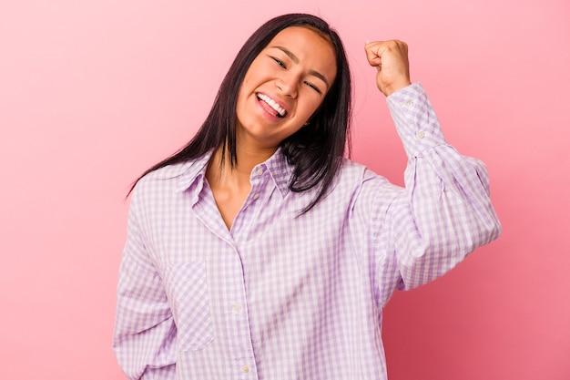 勝利、情熱と熱意、幸せな表現を祝うピンクの背景に分離された若いラテン女性。