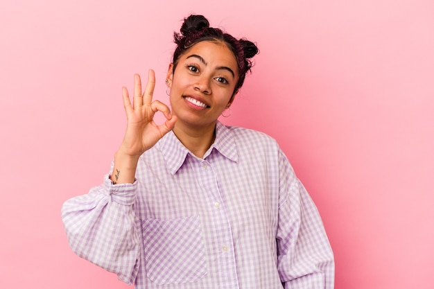 Молодая латинская женщина, изолированных на розовом фоне, веселая и уверенная, показывая одобренный жест.