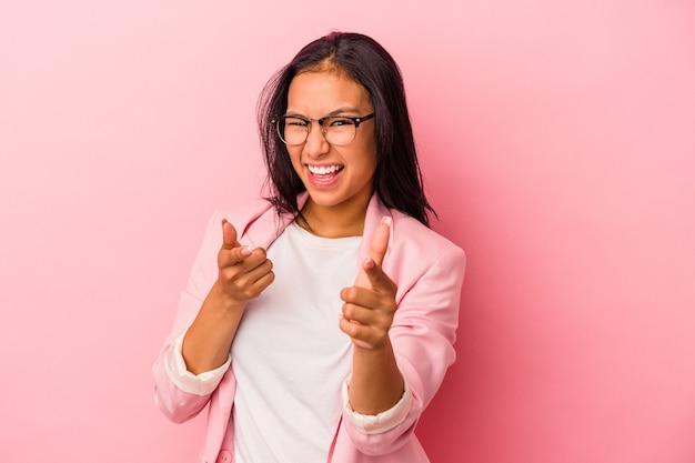 분홍색 배경에 격리된 젊은 라틴 여성이 앞을 가리키는 밝은 미소를 짓고 있습니다.