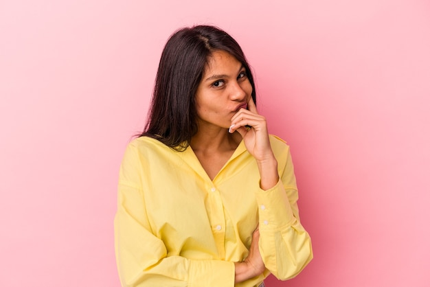 ピンクの背景に孤立した若いラテン女性は、ビジネスの方法を考え、戦略を計画し、考えています。