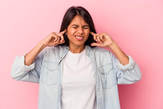 분홍색 배경에 고립된 젊은 라틴 여성은 큰 소리로 인해 스트레스를 받고 절망적으로 귀를 덮고 있습니다.