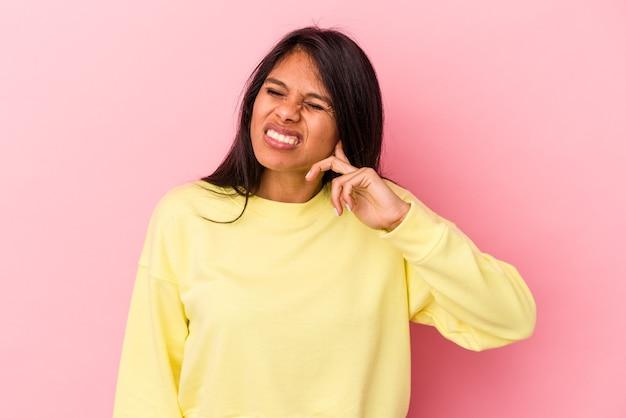 指で耳を覆っているピンクの背景に孤立した若いラテン女性は、大声で周囲にストレスと絶望的です。