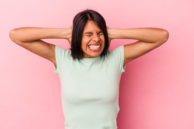 ピンクの背景に孤立した若いラテン女性は、あまりにも大きな音を聞かないように手で耳を覆っています。