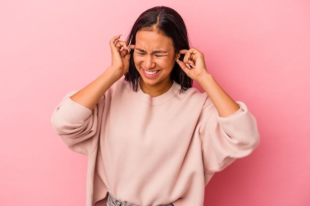手で耳を覆うピンクの背景に分離された若いラテン女性。
