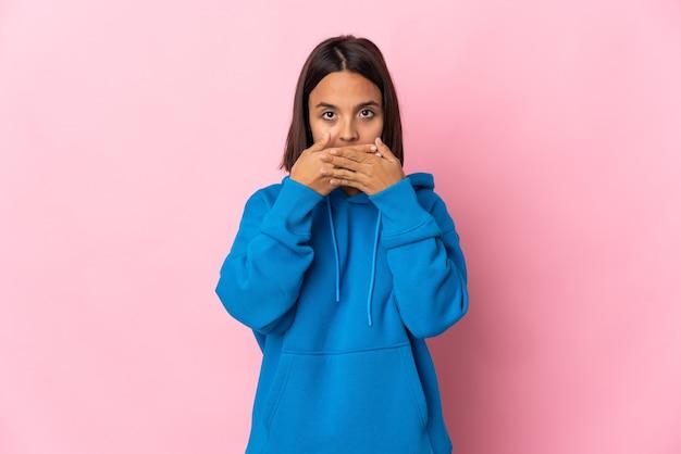 손으로 입을 덮고 분홍색 배경에 고립 된 젊은 라틴 여자