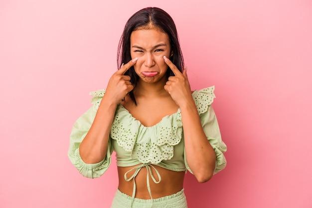 Молодая латинская женщина изолирована на розовом фоне плачет, недовольна чем-то, агонией и концепцией замешательства.