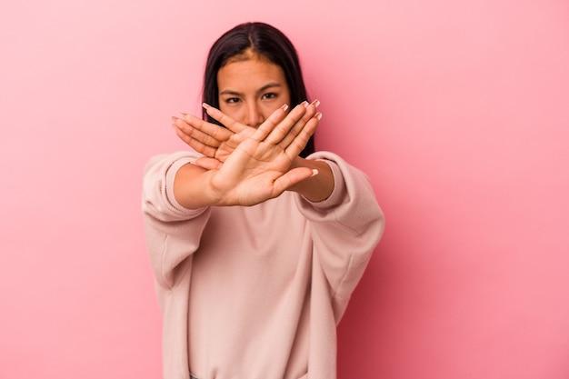 拒否ジェスチャーをしているピンクの背景に分離された若いラテン女性