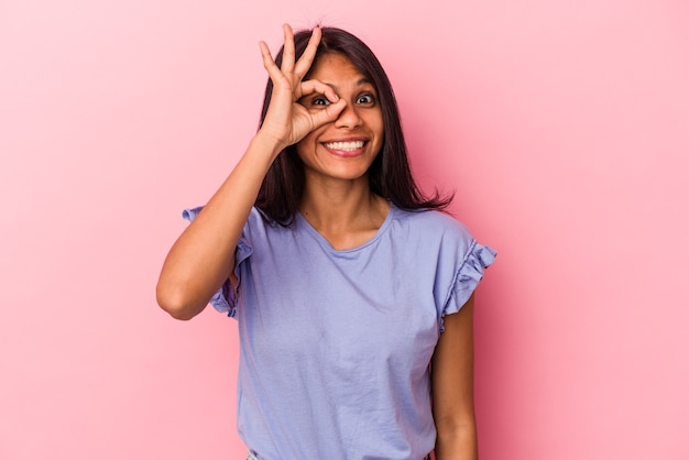 ピンクの背景に分離された若いラテン女性は、目に大丈夫なジェスチャーを維持して興奮しました。